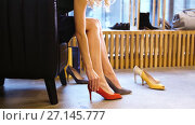 Купить «young woman trying heeled shoes at store», видеоролик № 27145777, снято 6 октября 2017 г. (c) Syda Productions / Фотобанк Лори