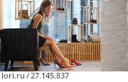 Купить «young woman trying heeled shoes at store», видеоролик № 27145837, снято 6 октября 2017 г. (c) Syda Productions / Фотобанк Лори