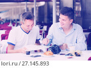 Купить «Male tourists with map talking and drinking coffee», фото № 27145893, снято 1 августа 2017 г. (c) Яков Филимонов / Фотобанк Лори