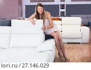 Купить «Adult girl sitting and testing new sofa», фото № 27146029, снято 5 сентября 2017 г. (c) Яков Филимонов / Фотобанк Лори