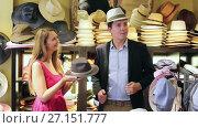 happy young female and man choosing hats in the store. Стоковое видео, видеограф Яков Филимонов / Фотобанк Лори