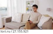 Купить «man with remote control watching tv at home», видеоролик № 27155921, снято 5 апреля 2020 г. (c) Syda Productions / Фотобанк Лори