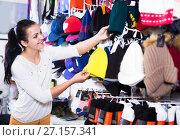 Купить «Woman choosing new knit cap», фото № 27157341, снято 22 ноября 2016 г. (c) Яков Филимонов / Фотобанк Лори