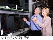 Smiling mature married couple choose for themselves home modern TV. Стоковое фото, фотограф Яков Филимонов / Фотобанк Лори