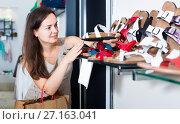 Купить «woman customer selecting shoes in footgear center», фото № 27163041, снято 26 сентября 2016 г. (c) Яков Филимонов / Фотобанк Лори