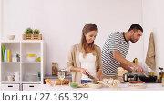 Купить «happy couple cooking food at home kitchen», видеоролик № 27165329, снято 17 июля 2019 г. (c) Syda Productions / Фотобанк Лори