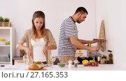 Купить «happy couple cooking and serving food at home», видеоролик № 27165353, снято 19 ноября 2017 г. (c) Syda Productions / Фотобанк Лори