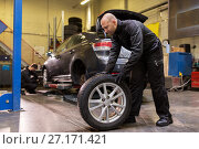 Купить «auto mechanic changing car tire at workshop», фото № 27171421, снято 21 сентября 2017 г. (c) Syda Productions / Фотобанк Лори
