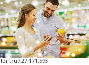 Купить «couple with smartphone buying oranges at grocery», фото № 27171593, снято 21 октября 2016 г. (c) Syda Productions / Фотобанк Лори
