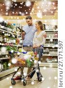 Купить «couple with wine and shopping cart at liquor store», фото № 27171597, снято 21 октября 2016 г. (c) Syda Productions / Фотобанк Лори