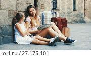 Купить «Young mother and daughter travelers sitting on ground near wall looking map and phone», видеоролик № 27175101, снято 23 августа 2017 г. (c) Яков Филимонов / Фотобанк Лори