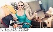 Купить «Smiling young female ready to depart for holiday», фото № 27176529, снято 21 марта 2017 г. (c) Яков Филимонов / Фотобанк Лори