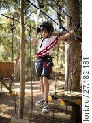 Купить «Determined boy crossing zip line», фото № 27182181, снято 9 мая 2017 г. (c) Wavebreak Media / Фотобанк Лори