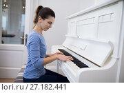 Купить «Beautiful woman playing piano», фото № 27182441, снято 30 августа 2017 г. (c) Wavebreak Media / Фотобанк Лори