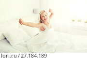 Купить «young woman stretching in bed at home bedroom», фото № 27184189, снято 25 февраля 2016 г. (c) Syda Productions / Фотобанк Лори