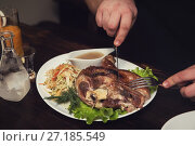 Man eats tasty dish of pork shank. Стоковое фото, фотограф Jan Jack Russo Media / Фотобанк Лори