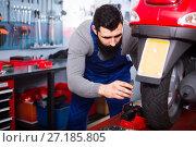 Купить «Worker repairing motorbike wheel», фото № 27185805, снято 17 октября 2019 г. (c) Яков Филимонов / Фотобанк Лори