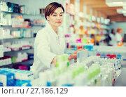 Купить «Female pharmacist arranging displayed assortment», фото № 27186129, снято 31 января 2017 г. (c) Яков Филимонов / Фотобанк Лори