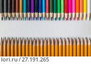 Купить «Цветные карандаши напротив графитовых карандашей на белой бумаге», фото № 27191265, снято 3 ноября 2017 г. (c) Сергей Васильев / Фотобанк Лори