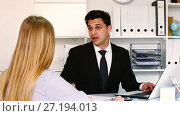 Купить «Smiling businessman in black suit talking to female colleague in office», видеоролик № 27194013, снято 29 апреля 2017 г. (c) Яков Филимонов / Фотобанк Лори