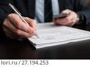 Бизнесмен подписывает деловые бумаги держа в руках телефон. Стоковое фото, фотограф Игорь Низов / Фотобанк Лори