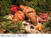 Рождественский натюрморт со сладостями, круассаном и яблоком под новогодней елкой. Стоковое фото, фотограф Николай Винокуров / Фотобанк Лори