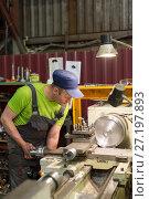 The turner processes the metal part on a mechanical lathe. (2017 год). Редакционное фото, фотограф Андрей Радченко / Фотобанк Лори