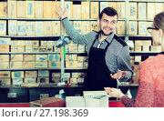 Купить «Seller assisting woman in choosing door hinges», фото № 27198369, снято 5 апреля 2017 г. (c) Яков Филимонов / Фотобанк Лори