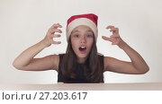 Beautiful happy girl teenager in a Santa Claus hat emotionally expresses a joyful surprise on white background stock footage video. Стоковое видео, видеограф Юлия Машкова / Фотобанк Лори