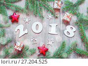 Купить «Happy New Year 2018 background with 2018 figures, Christmas toys, green fir tree branches. New Year 2018 holiday still life», фото № 27204525, снято 29 ноября 2016 г. (c) Зезелина Марина / Фотобанк Лори