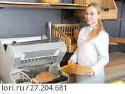 Купить «Girl baker cutting bread on machine», фото № 27204681, снято 20 октября 2018 г. (c) Яков Филимонов / Фотобанк Лори