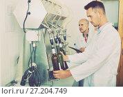 Купить «Portrait of male winery worker with bottling machinery on factor», фото № 27204749, снято 19 января 2018 г. (c) Яков Филимонов / Фотобанк Лори