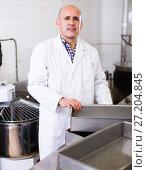 Купить «Worker standing near table in manufacture», фото № 27204845, снято 22 апреля 2017 г. (c) Яков Филимонов / Фотобанк Лори