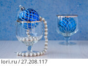 Купить «Thread of white pearls in a glass and a blue Christmas ball on a table», фото № 27208117, снято 28 октября 2017 г. (c) Катерина Белякина / Фотобанк Лори