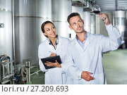 Купить «Man and woman employees on winery manufactory», фото № 27209693, снято 22 июля 2018 г. (c) Яков Филимонов / Фотобанк Лори