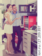 Купить «Smiling woman and husband choosing new microwave», фото № 27209897, снято 15 июня 2017 г. (c) Яков Филимонов / Фотобанк Лори