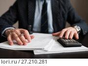Купить «Бизнесмен работает с калькулятором, сидя за деловыми бумагами», эксклюзивное фото № 27210281, снято 6 ноября 2017 г. (c) Игорь Низов / Фотобанк Лори