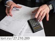 Купить «Мужчина считает на калькуляторе сидя за деловыми бумагами», эксклюзивное фото № 27210289, снято 6 ноября 2017 г. (c) Игорь Низов / Фотобанк Лори