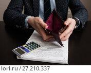 Банкрот. Бизнесмен раскрывает пустой кошелёк на фоне документов и калькулятора. Стоковое фото, фотограф Игорь Низов / Фотобанк Лори