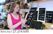 cheerful blonde woman looking to jewelry stand and chooses errings in store. Стоковое видео, видеограф Яков Филимонов / Фотобанк Лори