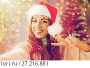 Купить «happy woman taking selfie over christmas tree», фото № 27216881, снято 15 октября 2016 г. (c) Syda Productions / Фотобанк Лори