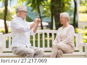 Купить «old woman photographing man by smartphone in park», фото № 27217069, снято 16 июля 2017 г. (c) Syda Productions / Фотобанк Лори
