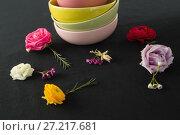 Купить «Bowls and flowers arranged on a black themed table», фото № 27217681, снято 14 июня 2017 г. (c) Wavebreak Media / Фотобанк Лори