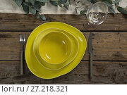 Stack of various dinnerware with cutlery and empty glass. Стоковое фото, агентство Wavebreak Media / Фотобанк Лори