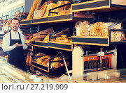 Купить «Male shop assistant demonstrating delicious loaves of bread in bakery», фото № 27219909, снято 26 января 2017 г. (c) Яков Филимонов / Фотобанк Лори