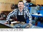 Купить «Male worker demonstrating workplace and tools in shoe», фото № 27219953, снято 2 февраля 2017 г. (c) Яков Филимонов / Фотобанк Лори