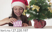 Купить «Beautiful naughty girl teenager in a Santa Claus hat secretly puts a gift under the New Year tree on white background stock footage video.», видеоролик № 27220197, снято 1 ноября 2017 г. (c) Юлия Машкова / Фотобанк Лори