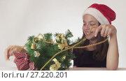Купить «Beautiful naughty teenager girl trying to dress up a New Year tree, but the Christmas tree always falls, violent emotions on white background stock footage video», видеоролик № 27220201, снято 30 октября 2017 г. (c) Юлия Машкова / Фотобанк Лори