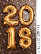 Купить «Bright metallic gold balloons figures 2018, Christmas, New Year Balloon with glitter stars on dark wood table background», фото № 27220473, снято 19 ноября 2017 г. (c) Сергей Тимофеев / Фотобанк Лори
