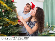 Купить «Happy smiling couple decorating Christmas tree», фото № 27226081, снято 21 ноября 2018 г. (c) Яков Филимонов / Фотобанк Лори
